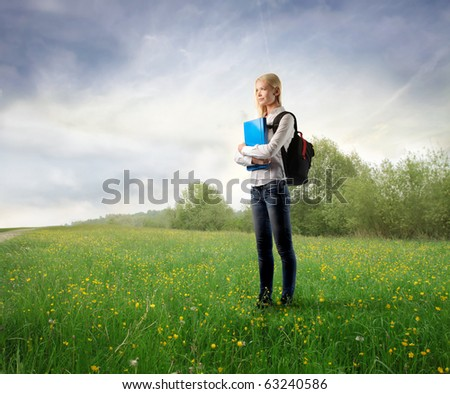 Student standing on a green meadow - stock photo