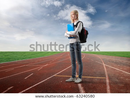 Student standing on a running track - stock photo