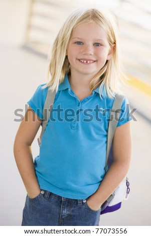 Student standing outdoors smiling (high key) - stock photo