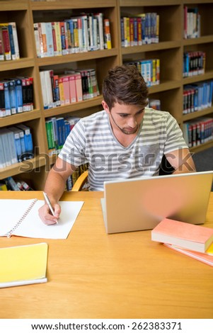 Student studying in the library with laptop at the university - stock photo