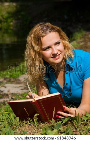 Student studying on the grass - stock photo