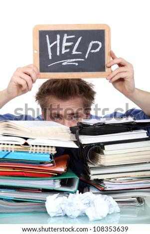 Student swamped under paperwork - stock photo