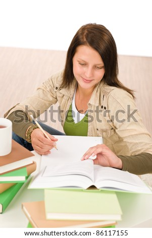 Student teenager happy girl write homework with book - stock photo