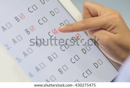 student testing in exercise, exams answer on a tablet with multiple-choice questions by finger clicking. - stock photo