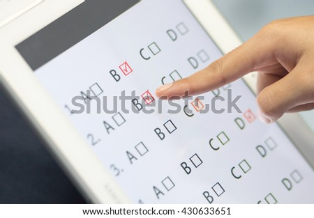 student testing in exercise, exams answer on a tablet with multiple-choice questions by finger clicking, online learning - stock photo