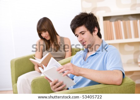 Student - two teenager reading book in lounge, sitting on armchair