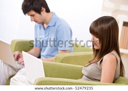 Student - two teenager with laptop in living room, on green armchair