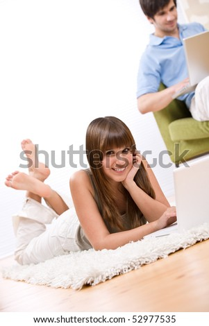 Student - two teenager with laptop in living room, on green armchair - stock photo