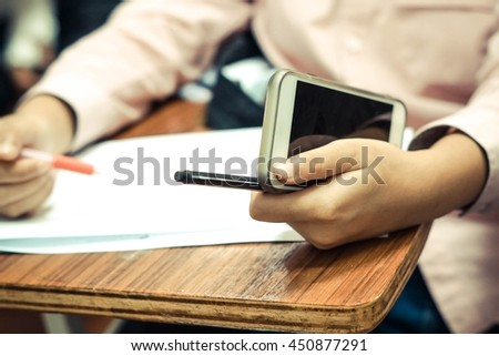 Student using a smartphone while studying / Student with martphone addiction concept