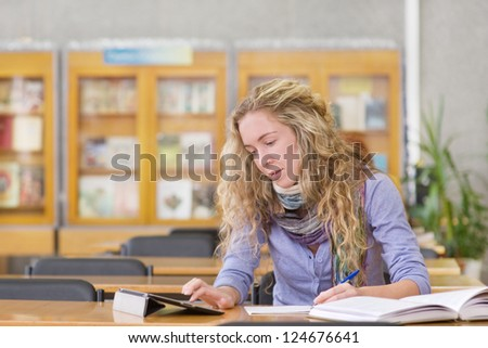 student using a tablet computer in a library