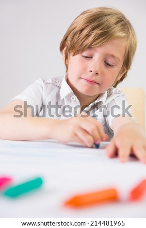 Student using crayons to draw on white background