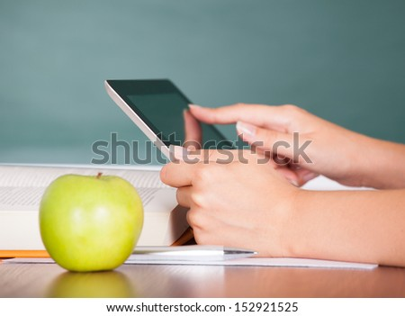 Student using digital tablet beside green apple while studying - stock photo