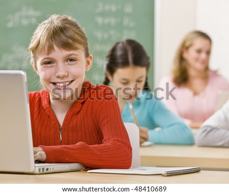 Student using laptop in classroom - stock photo