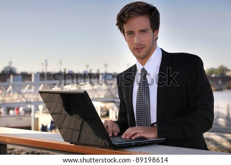 Student using laptop outdoors - stock photo