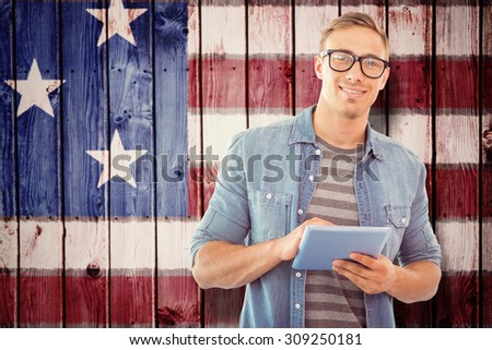 Student using tablet against composite image of usa national flag