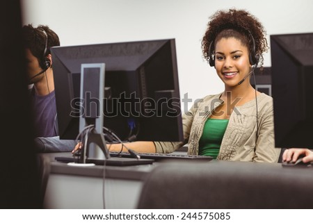 Student wearing headset looking at camera at the university - stock photo