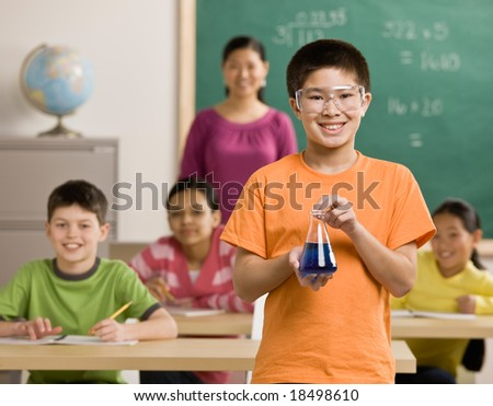 Student wearing safety goggles holds beaker of liquid in science classroom