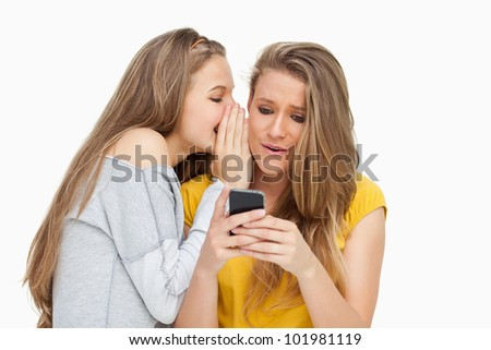 Student whispering to her friend who's texting on her phone against white background