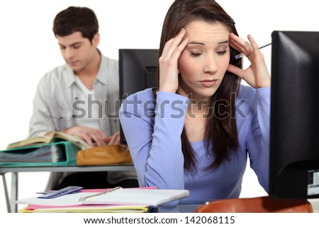 Student with a headache at a computer - stock photo
