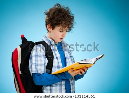 Student with backpack reading book - stock photo