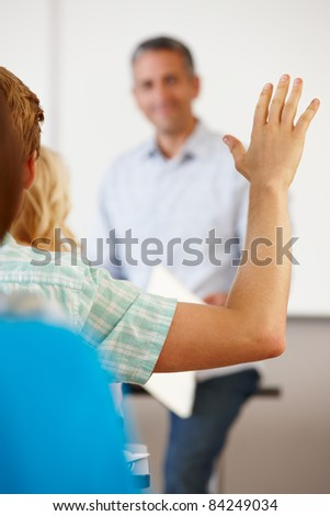 Student with hand up in class - stock photo