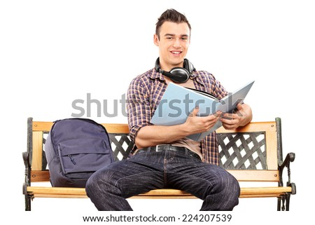 Student with headphones reading a book seated on a bench isolated on white background - stock photo
