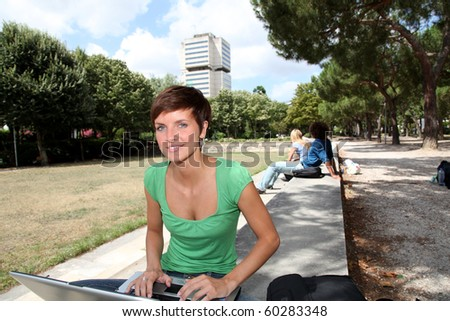 Student with laptop computer in college park - stock photo