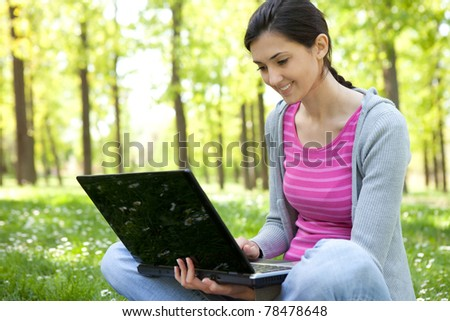 student with laptop smiling while chatting or checking email in the park - stock photo