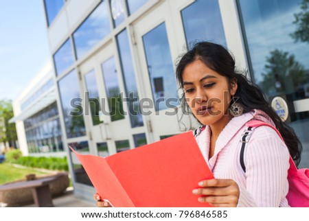 Student with notebook next to college
