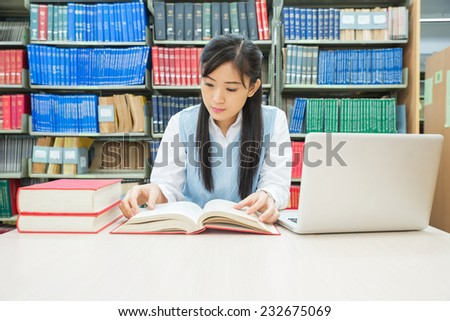 Student with open book reading it in college library - stock photo