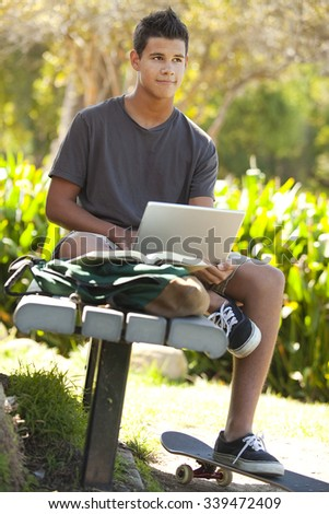 Student with skateboard and backpack at a park