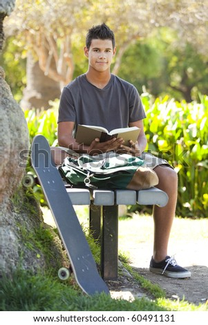 Student with skateboard and backpack at a park - stock photo