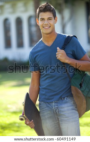 Student with skateboard and backpack outside school - stock photo
