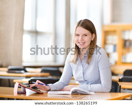 student with tablet computer in library. looking at camera