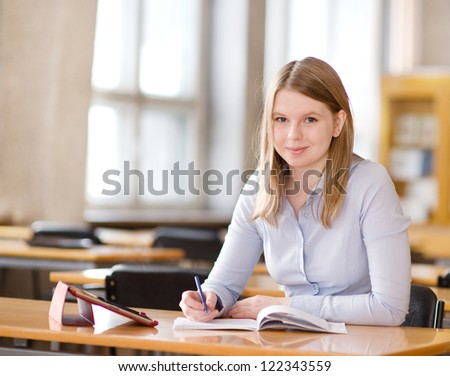 student with touchpad in library. looking at camera - stock photo