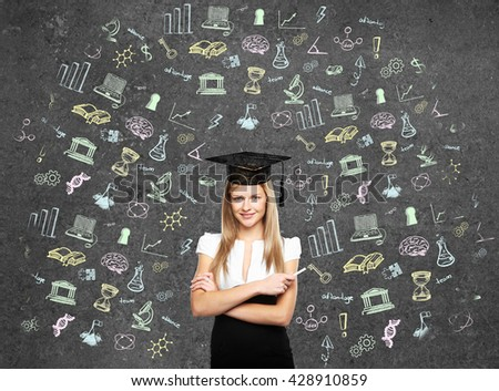 student woman in bachelor hat and drawing education simbol on wall - stock photo