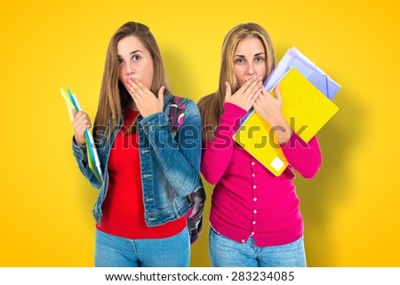 Student women doing surprise gesture over colorful background - stock photo