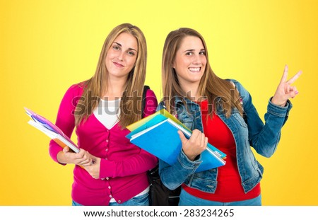 Student women doing victory gesture over colorful background - stock photo