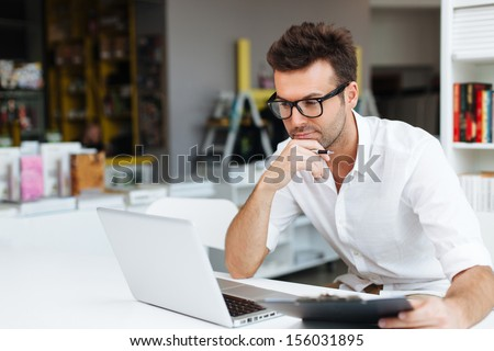 Student working on laptop in library - stock photo