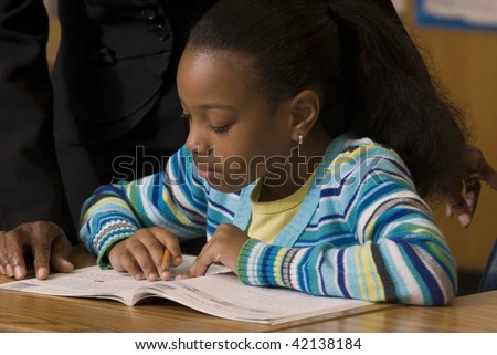 Student works in her workbook as teacher look over her shoulder - stock photo