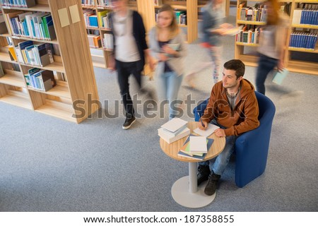 Student writing notes with classmate walking in library blur motion - stock photo