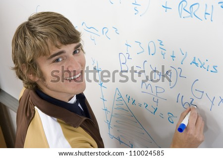 Student writing on board - stock photo