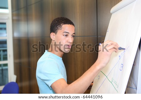 Student writing on the blackboard in classroom - stock photo
