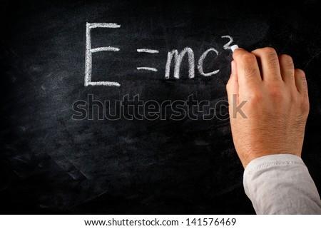 student writing on the chalkboard Einstein's formula e=mc2 - stock photo