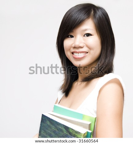 Student. Young Asian girl standing with books. - stock photo