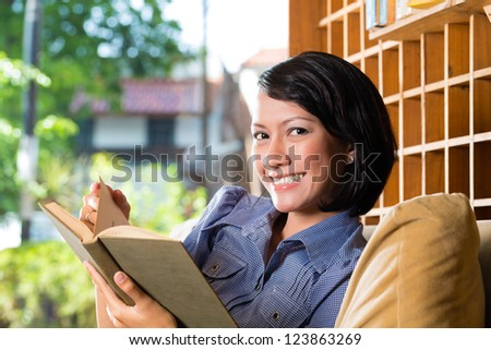 Student - Young asian woman or girl sitting on a sofa with a cup of coffee reading a book, she is learning - stock photo