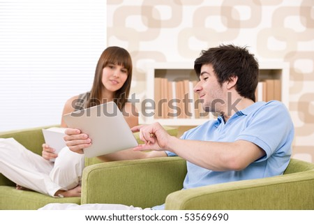Student - young man with touch screen tablet computer sitting on armchair in lounge with woman