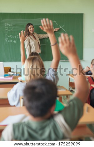 Students answering the teacher's question in a maths lesson. - stock photo