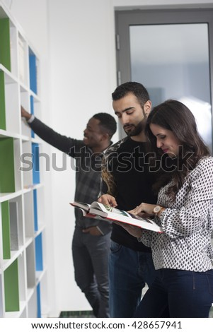 Students are looking for books for their lectures in the university library - stock photo