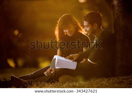 Students are reading a book under a tree the morning.lens flare - stock photo